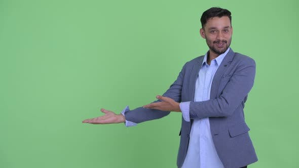 Thumbnail for Happy Young Bearded Persian Businessman Presenting Something