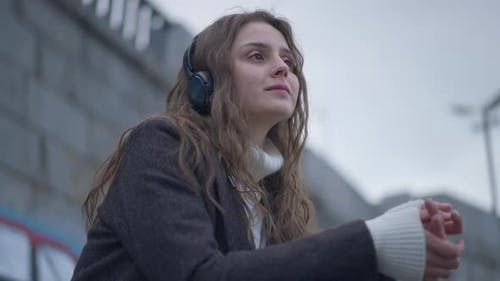 Young Smiling Relaxed Woman Listening to Calm Music in Headphones Resting Outdoors on Urban