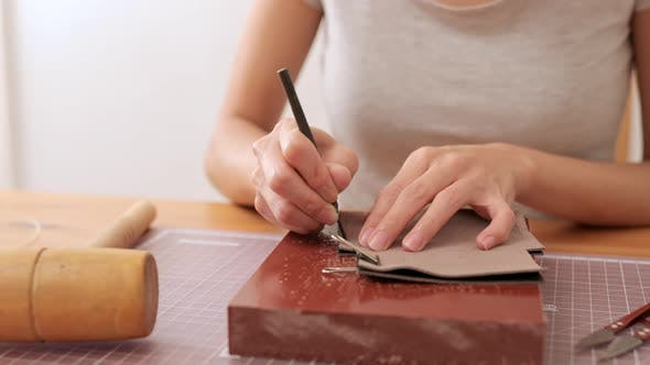 Thumbnail for Woman sewing leather at home
