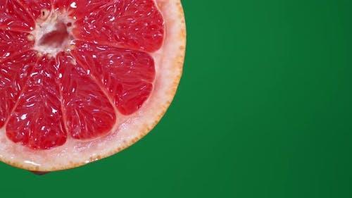 Mit Scheiben reifer roter Grapefruit tropfen Sie einen Tropfen Saft.