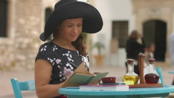 Thumbnail for Junge weibliche Schriftstellerin macht Notizen im Notizbuch, genießen Ruhe im Café im Freien