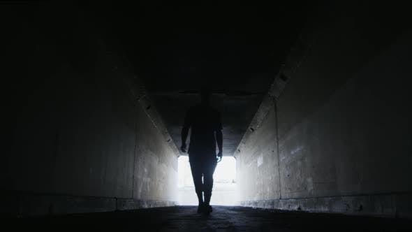 Thumbnail for Silhouette of Man Walking Towards Camera Inside LA Tunnel