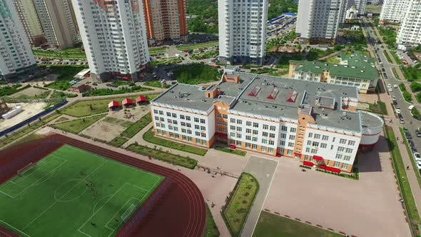 Thumbnail for Sports Stadium in Schoolyard on High Rise Buildings. Aerial View Football Field