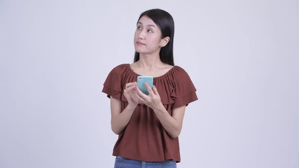 Cover Image for Happy Beautiful Asian Woman Thinking While Using Phone