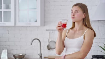 Young woman drinks fresh juice. Lovely girl with a glass of tasty red juice in the kitchen.