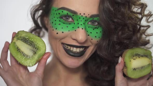Thumbnail for Portrait Pretty Smilling Curly Girl with Bright Make Up Holding Two Halves of Kiwi