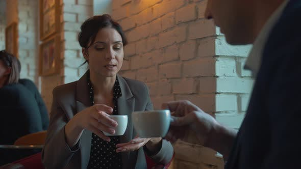 Thumbnail for Business Partners Drink Coffee and Chat in Cafe