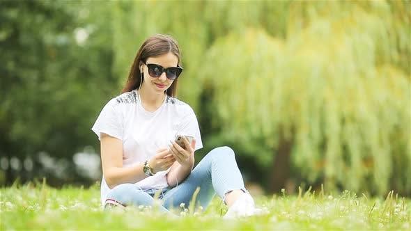 Thumbnail for Niedliche Frau liest Textnachricht auf Handy während Sitzen im Park.