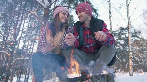 a Pair of Young People in Red Shirts in the Woods Warm Their Hands By the Fire a Winter Picnic