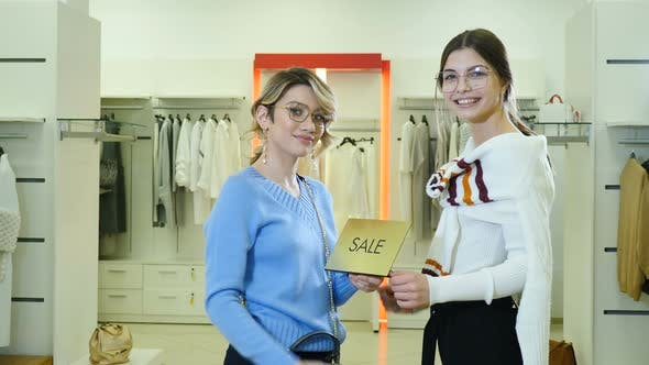 Portrait of Pretty Stylish and Fashionable Female Customers Holding Silver Sale Sign in Fashion