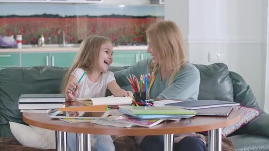 Thumbnail for Cheerful Caucasian Mother and Daughter Hugging As Sitting at the Table at Home. Smiling Parent