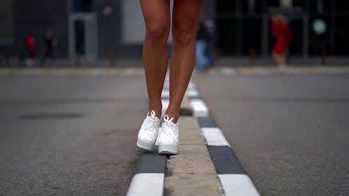 Women's Feet in White Highsoled Shoes Walk on a Very Narrow Sidewalk