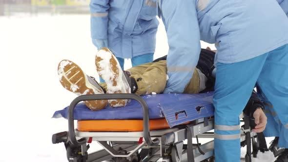 Paramedics Putting Patient on Stretcher