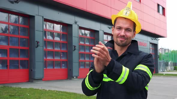 A Young Firefighter Claps His Hands and Smiles at the Camera, a Fire Station in the Background