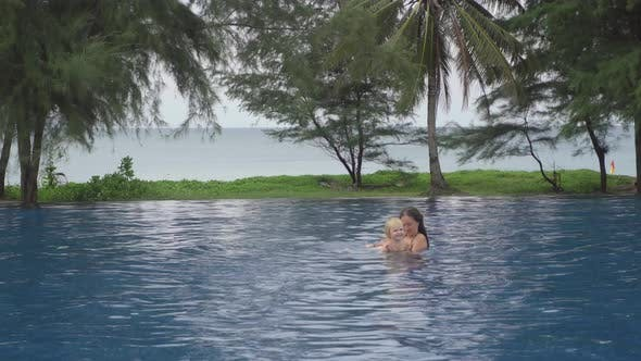 Cover Image for Mom with a Two-year-old Daughter in Hotel Pool Near Ocean