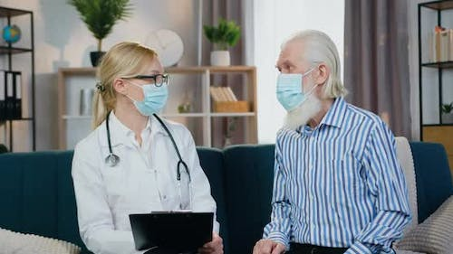 Bearded Man in Mask Talking with His Local Female Doctor and Telling About Well-Being