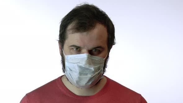 Thumbnail for Man in Medical Mask Raises Head, Looks Tensely at Camera. Panic of Coronavirus