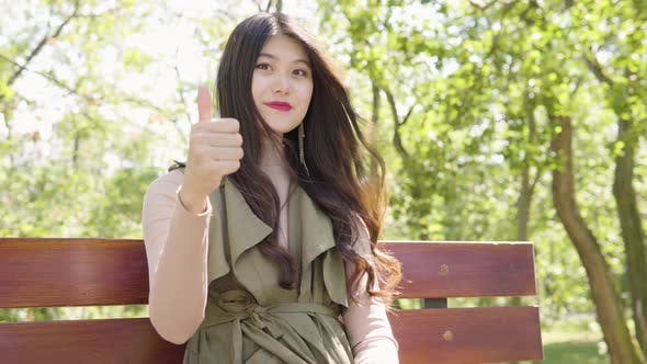Young Asian Woman Shows Thumb Up To Camera Nods Smile As She Sits Bench