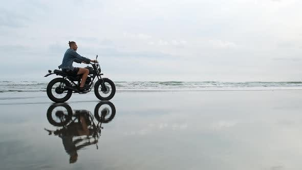 Thumbnail for Young Handsome Hipster Man Riding Modern Custom Motorcycle Racer on the Black Sand Beach Near the