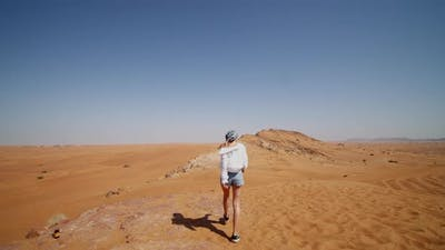 Following a Young Woman Walking on Sand Dunes