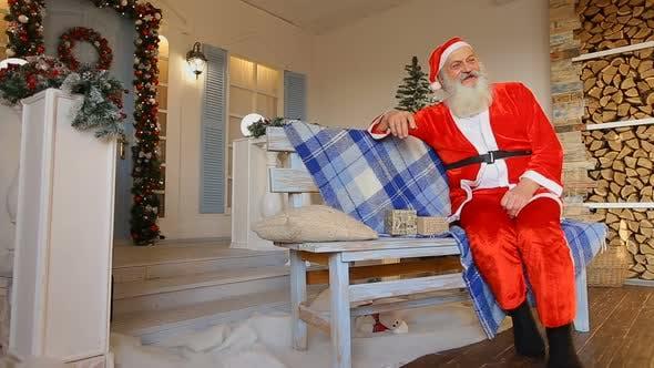 Thumbnail for Weihnachtsmann erzählt faszinierende Geschichte, sitzend auf Bank im Hof des Hauses Dekoriert für