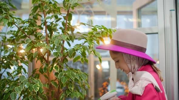 Gardener Girl in Pink Hat Spraying Plants in Indoor Orangery