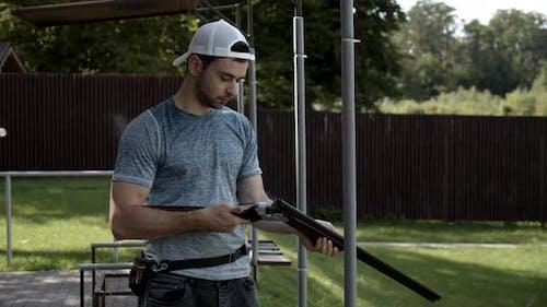 Ein junger Mann stürnt ein Gewehr