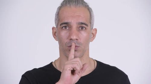 Handsome Persian Man with Finger on Lips Against White Background