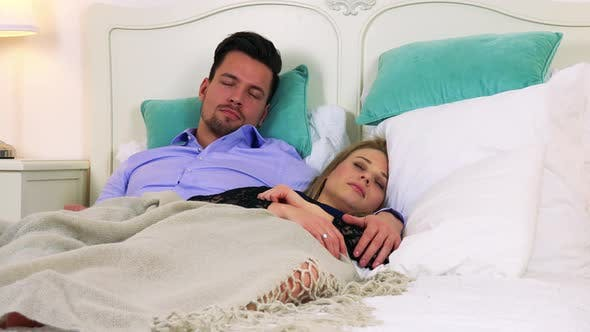 Thumbnail for A Young Attractive Couple Sleeps in a Bed Under a Clanket, Bedside Tables with Lamps on the Sides