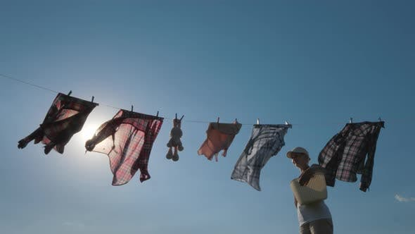 Thumbnail for Housewife Looks at How Washed Laundry Is Dried on a Rope