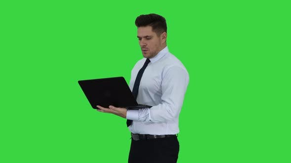 Thumbnail for Businessman Pressing Play Button To Start or Initiate Projects or Presentation on Laptop on a Green