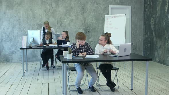 Thumbnail for Group of Business Children Sharing Ideas, Using Laptop and Tablet Computers, Working in Office