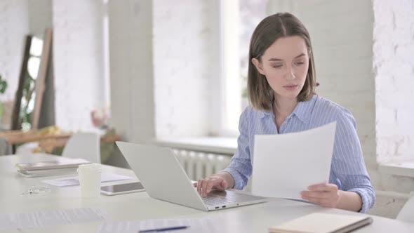Thumbnail for Focused Young Woman Reading Documents and Working on Laptop