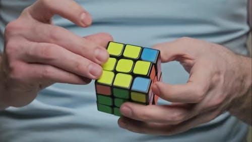 Man Hands Solving Rubik's Cube Puzzle. Puzzle Game.
