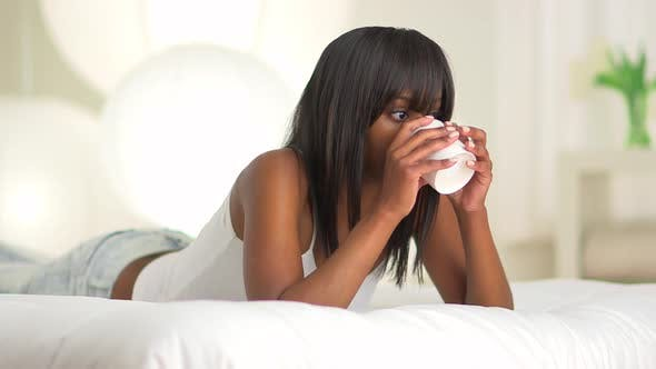 Happy black woman lying on bed drinking coffee