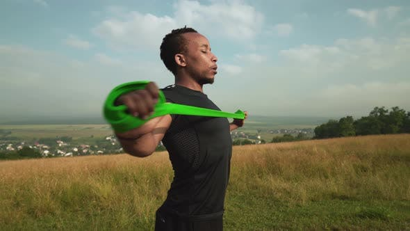 Thumbnail for Side View of African Man Working Out with Rubber Expander