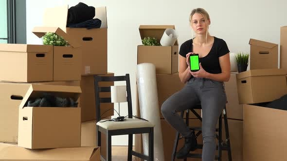 Thumbnail for A Moving Woman Sits on a Chair in an Empty Apartment, and Shows a Smartphone with a Green Screen