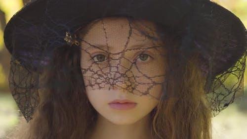 Nahaufnahme eines rothaarigen kaukasischen Mädchens in Halloween Hexenhut stehend im Herbst Park
