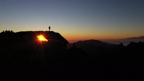 Thumbnail for Silhouetted People On Mountain Watching Sunset