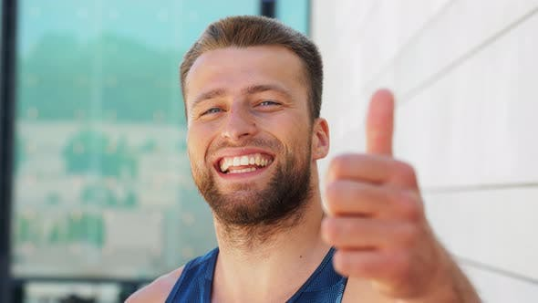 Thumbnail for Portrait of Smiling Young Man Showing Thumbs Up