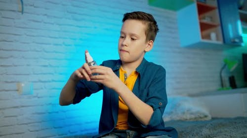 Boy using hand sanitizer alcohol spray rub for hands hygiene in home