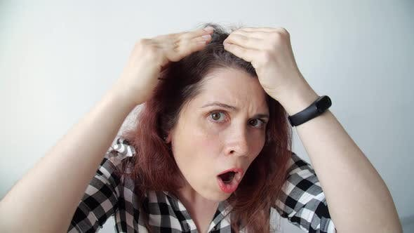 Thumbnail for Young Frustrated Woman Looks in the Mirror and Plucks a Grey Hair From Her Head. Concept Photo of