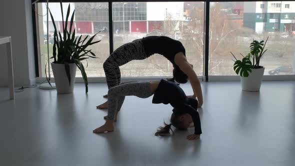 Little Girl with Mom are Engaged in Yoga Indoors