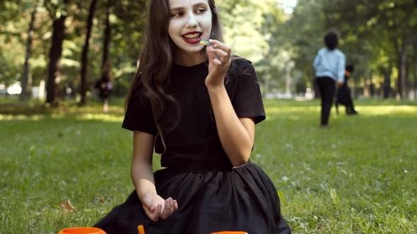 Niedliches Mädchen trägt Dämonen-Kostüm Essen Süßigkeiten