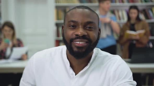 Thumbnail for Positive Bearded Young Black-Skinned Man Looking at Camera in the Library