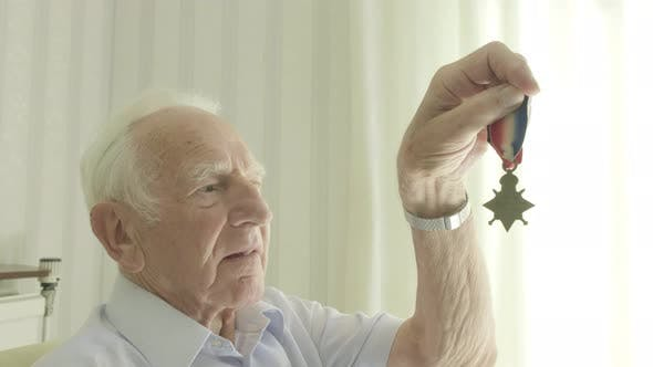 Thumbnail for Senior man looking at an old medal