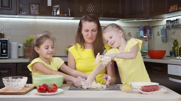 Thumbnail for Mom and Children Cook Pizza in the Kitchen. Children Help Their Mother To Cook. Stylish Family