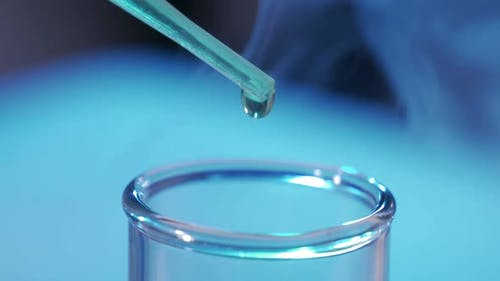 In a Laboratory a Scientist with a Pipette Analyzes a Colored Liquid