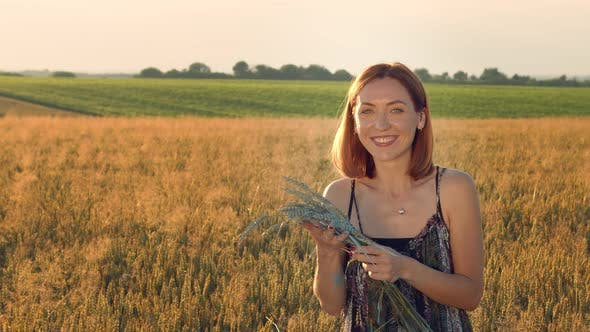 Thumbnail for Portrait of a Woman Artist Who Shows Emotions and Smiles. Woman Holds in Her Hands Ears of Wheat