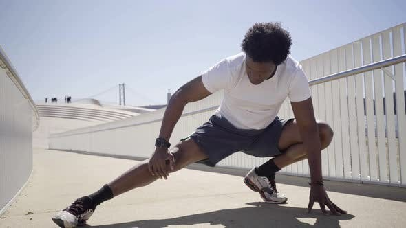 Cover Image for Concentrated African American Man Stretching Legs on Bridge